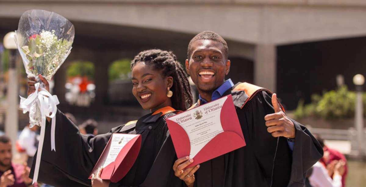 UOttawa graduates, smiling and holding their diplomas