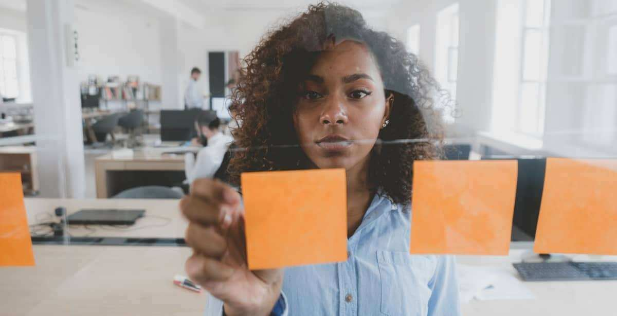African American female employee looking onto a glass wall with sticky notes